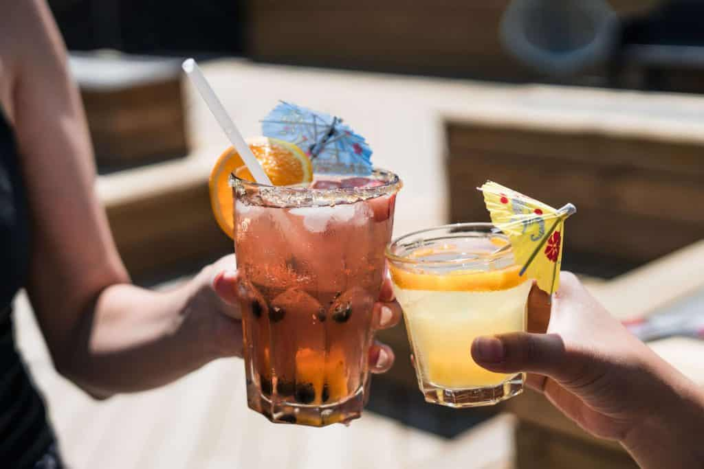 Cheersing with two cocktails | 12 Drinks From Around the World to Inspire Wanderlust