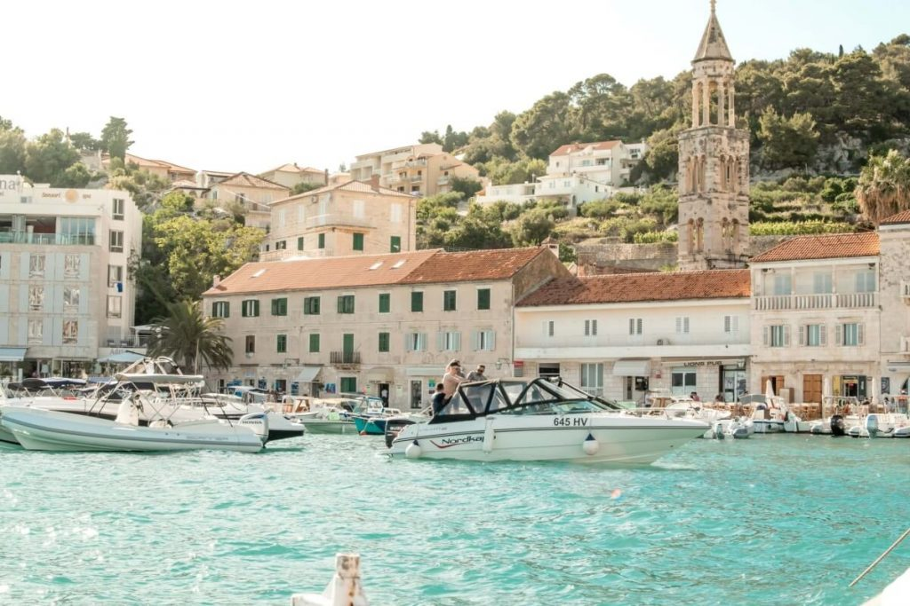 A view of Hvar Town's waterfront promenade on a bright and sunny summer day.