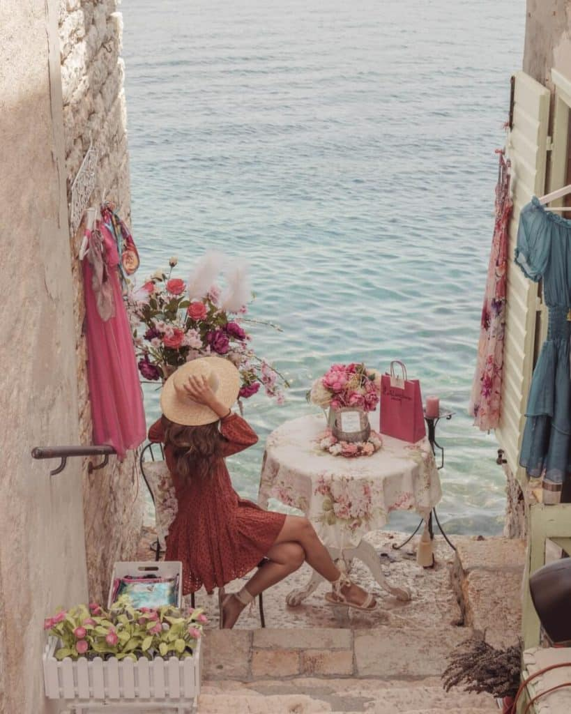 Girl sitting on a charming terrace in a summer dress wearing a straw hat overlooking the Adriatic Sea in Rovinj, Croatia.