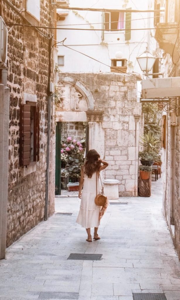 Solo female traveler wandering around Trogir, Croatia