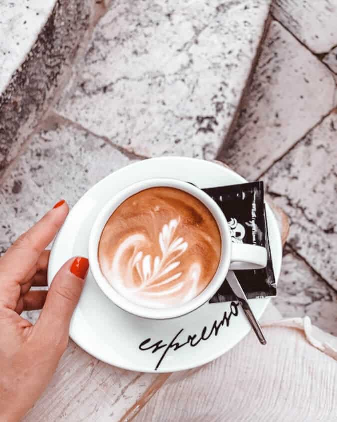 Life in Croatia | woman's hand holding a coffee cup over a stone terrace