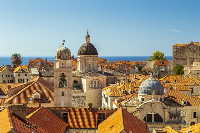 A beautiful view of the orange tiled rooftops in Dubrovnik, with the Adriatic Sea visible in the background.