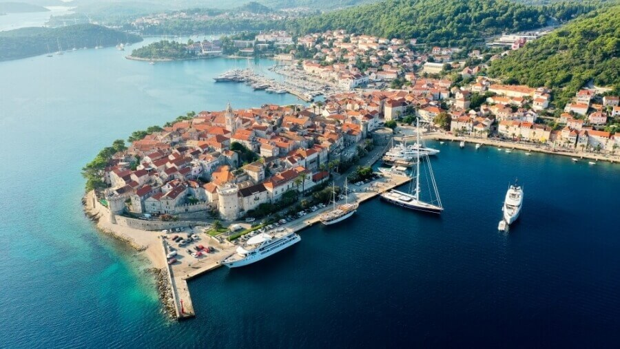 A spectacular aerial view of Korcula's Old Town with views of orange tiled rooftops, boats, and surrounding natural greenery.