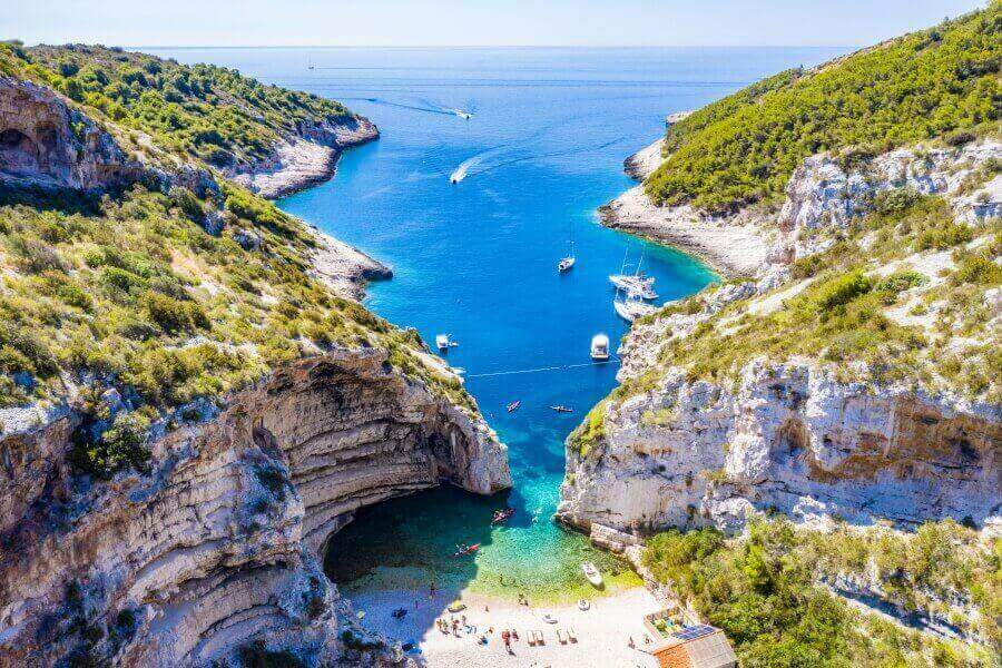 A stunning view of Stiniva Beach from the top of the hill featuring a sparkling blue Adriatic Sea and rugged cliffside that encompasses the beach.