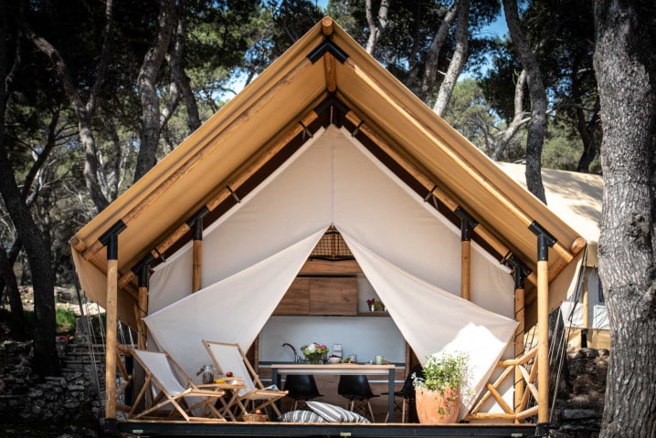 A view of the front of an open tent made up of natural wooden beams and cream-colored material. This luxurious tent also features a front porch with comfortable sun loungers.