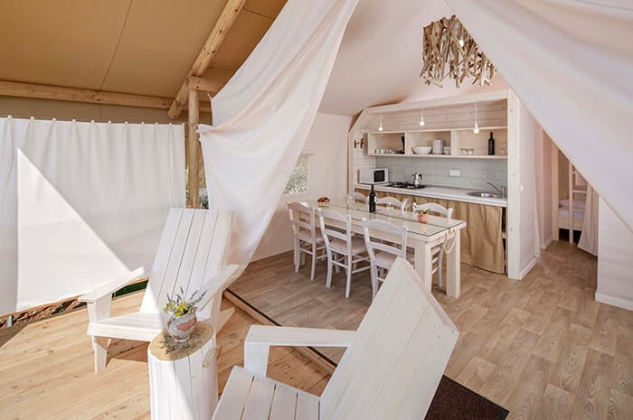 Luxury camping in Croatia | A photo of the tent kitchen decorated in beautiful white wood furnishings.