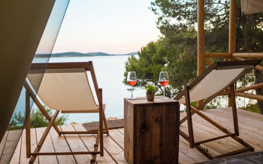 A stunning view of the Adriatic Sea from the terrace of a luxury tent on the island of Obonjan in Croatia. In the foreground of the photo are two sun loungers, a wooden table, and two glasses of red wine.