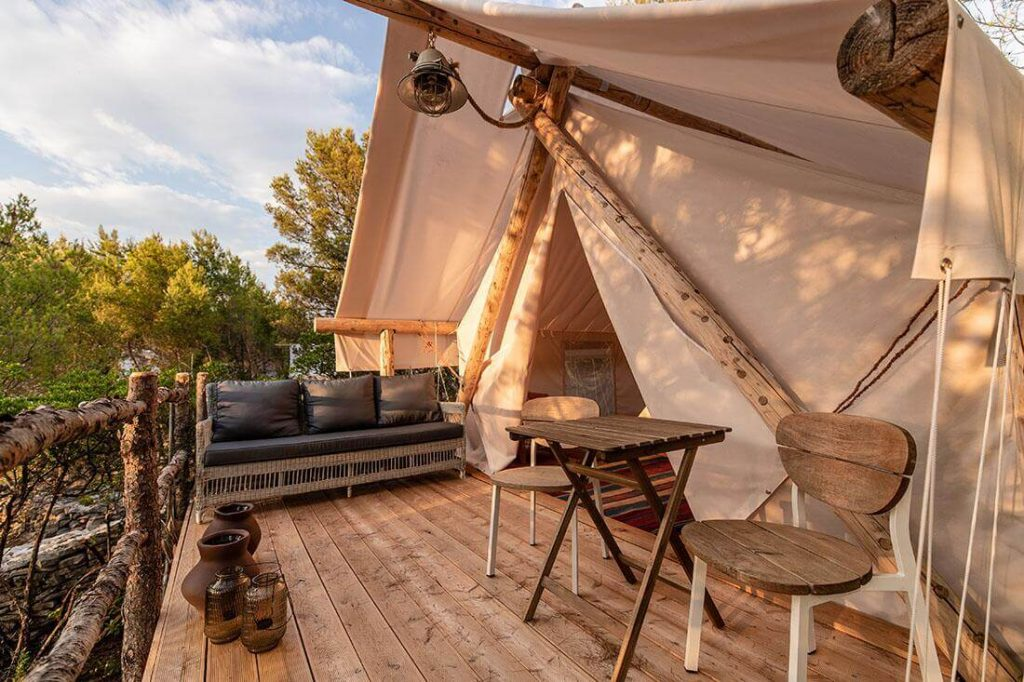 A gorgeous luxury tent featuring a wooden front porch on the island of Hvar | Luxury Camping in Croatia