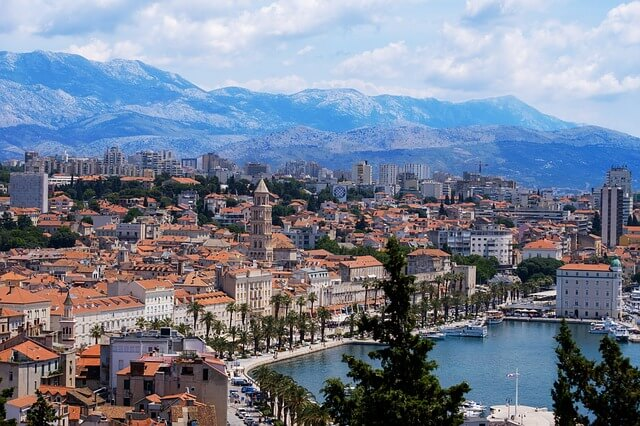 A gorgeous view of the Split waterfront promenade with beautiful mountains in the background.