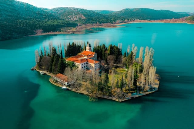 A bird's eye view of Visovac Island in Krka National Park. The small island is home to a monastery and is surrounded by stunning blue water.