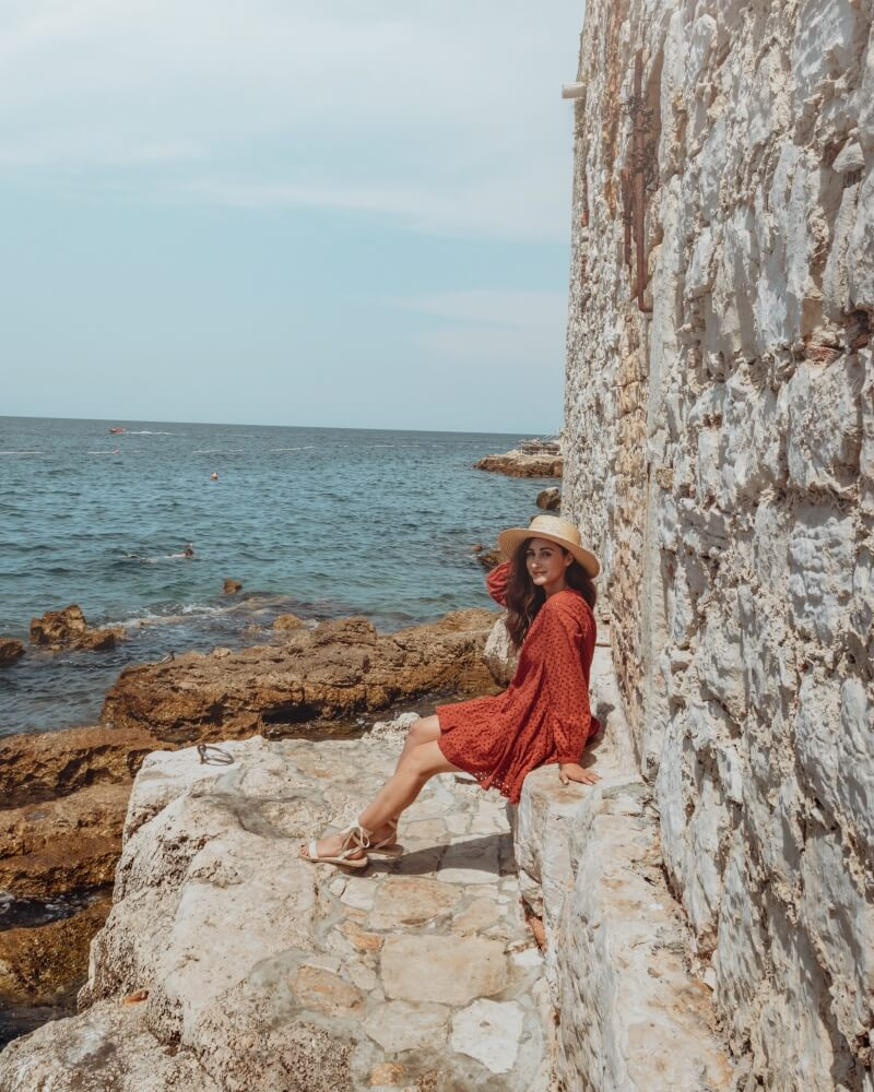 Girl wearing an orange dress and summer hat while sitting on a stone wall on the shores of the Adriatic Sea in Croatia.